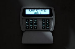 Alarm Panel Activated. A 3D render of a home security keypad access panel with buttons and an illuminated screen displaying a break in or security breach Royalty Free Stock Photo