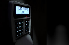 Alarm Panel Activated. A 3D render of a home security keypad access panel with buttons and an illuminated screen displaying a break in or security breach Stock Photography