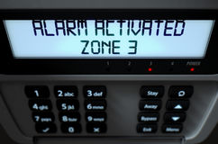 Alarm Panel Activated. A 3D render of a home security keypad access panel with buttons and an illuminated screen displaying a break in or security breach Stock Photos