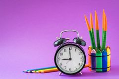 Alarm set at 9 o`clock, colorful cactus, rainbow pencils, working school drawing concept. Ultraviolet background Stock Photo