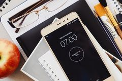 Alarm on the smartphone ringing at seven in the morning, school supplies, glasses and apple royalty free stock photos