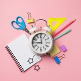 Alarm with supplies. Back to school theme royalty free stock photography