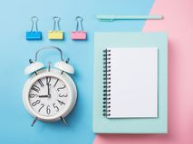 Alarm with supplies on color block background. Pastel minimalism. Alarm with supplies on color block, blue and pink background. Pastel minimalism royalty free stock images