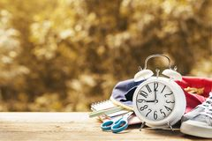 Alarm with supplies on fall background. Back to school theme royalty free stock images