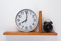 Alarm and wall clock at wooden shelf. On white background stock photos