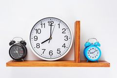 Alarm and wall clock at wooden shelf. On white background royalty free stock photography