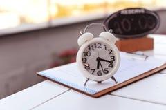 Alarma blanca del reloj con una placa giratoria en la tabla afuera en un res imagenes de archivo