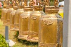 Alarma colgante Ejecución grande de la campana de oro en filas en un haz de acero Imágenes de archivo libres de regalías