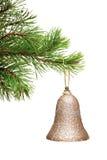 Alarma del oro que cuelga en una ramificación verde del árbol de navidad Imagenes de archivo
