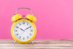 Alarma del reloj en el escritorio de madera y el fondo rosado de la feminidad imagen de archivo