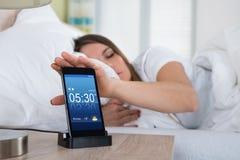 Alarma el dormitar de la mujer en la pantalla del teléfono móvil fotos de archivo libres de regalías