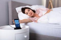 Alarma el dormitar de la mujer en el tel?fono m?vil imágenes de archivo libres de regalías
