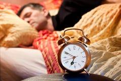 Alarma perezosa de la estela del sueño del hombre del reloj fotografía de archivo