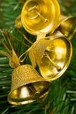 Alarmas de oro en el árbol de navidad Imágenes de archivo libres de regalías