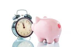 Alarmclock med piggybank på vit bakgrund Royaltyfri Bild