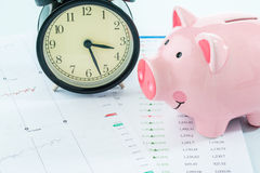 Alarmclock with piggybank, stock market. Alarmclock with piggybank on white background Stock Photo