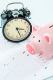 Alarmclock with piggybank, stock market. Alarmclock with piggybank on white background Stock Image