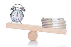Alarmclock and stacked dollar bundles balancing on seesaw Stock Photo