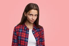 Alarmed, discontented young girl looks under her brows, wary and apprehensive. Girl in a red plaid shirt frowns and stares at the camera. Teenager fourteen stock photos