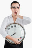 Alarmed, shocked business woman holding a large clock. White iso Stock Photography