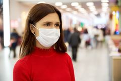 An alarmed young girl frowns and looks away. she is in the Mall and is afraid of infection. stock photography