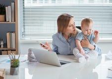 Alarmerad moder som tar omsorg av ungen i lägenhet Arkivbilder