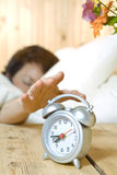 Alarming. Close up view of  table clock and woman sleeping on back Stock Photos