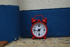 Alarming. Miniature alarm clock against rendered wall Stock Image