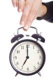 Alarmuhr, die durch Hand der Frau angehalten wird. Lizenzfreie Stockfotos