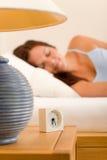Alarmuhr-Frau, die im weißen Bett schläft Stockbilder