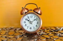 Alarmuhr und Münzen Stockfotografie