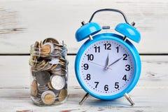 Alarmuhr und Münzen Lizenzfreies Stockfoto