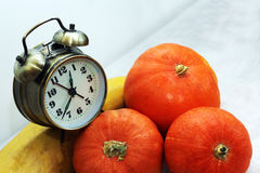 Alarrm clock and pumpkin Stock Photos
