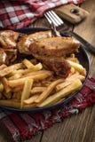Alas de pollo cocidas con las patatas fritas fotografía de archivo