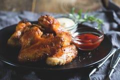 Alas de pollo con la salsa Imagenes de archivo