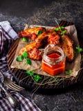 Alas de pollo con la salsa de tomate caliente en una tajadera Imagen de archivo