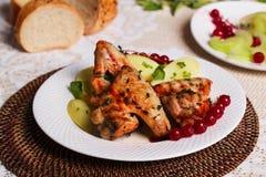 Alas de pollo con las patatas y los arándanos en la placa, aún vida en el restaurante Imagen de archivo libre de regalías