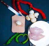 Alas de pollo crudas con las hierbas en una coliflor transparente del cuenco con los tomates y las hierbas Fotos de archivo libres de regalías
