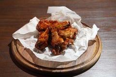 Alas de pollo en la salsa caliente, preparada especialmente para la cerveza Alas cocidas pollo en fondo de madera Foto de archivo