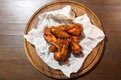 Alas de pollo en la salsa caliente, preparada especialmente para la cerveza Alas de pollo en salsa caliente en una placa de mader Imagenes de archivo