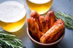 Alas de pollo frito con la cerveza en un fondo gris oscuro Fotografía de archivo
