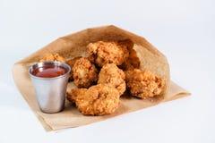 Alas de pollo frito con la salsa de tomate en un fondo blanco imagen de archivo