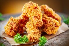 Alas de pollo frito curruscantes en la tabla de madera