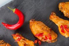 Alas de pollo frito en una placa negra de la pizarra Fotos de archivo