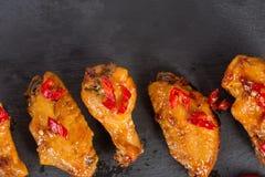 Alas de pollo frito en una placa negra de la pizarra Fotografía de archivo libre de regalías