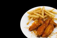 Alas de pollo y patatas fritas calientes Fotos de archivo libres de regalías