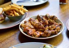 Alas y Chips Placed asados a la parrilla de pollo en el ` s del restaurante que cenan Tabl Imagen de archivo libre de regalías