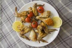 Alas y piernas de pollo con las rebanadas y el tomate del limón Foto de archivo libre de regalías