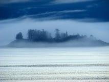 Alaska ö i molnen Arkivfoto