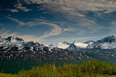 Alaska Chugach Mountains Ranges in Spring. Meadows green from melting snow and glaciers in early spring in the Chugach Mountains National forest near Valdez and stock images